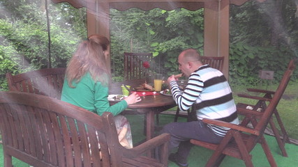 couple eat backed meat at table with candle in garden gazebo.