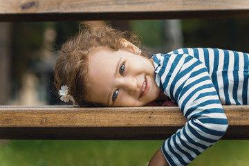 Portrait of little girl lying on bench in a park