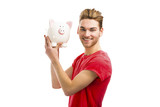 Handsome young man holding a piggy bank