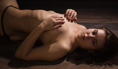 Naked sexy woman lying on a floor