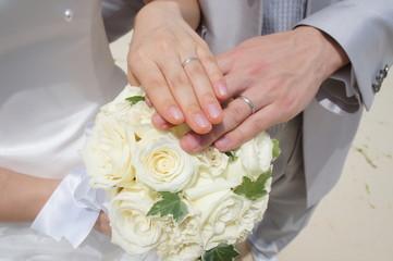 結婚式でブーケに手を沿える新郎と新婦