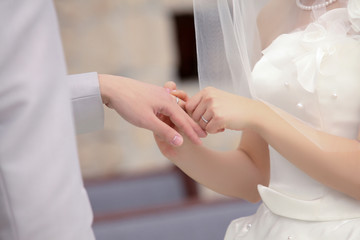 結婚式で指輪交換する新郎と新婦