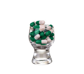 A glass of pills and capsules on white background