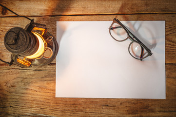 White paper on a wooden table with glasses, old lamp