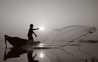 Fisherman of Bangpra Lake in action when fishing.(Sepia Style)