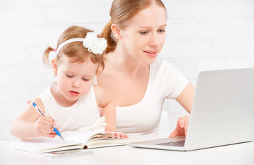happy family mother and child baby at home working on computer