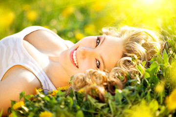 Beautiful young woman lying on a field, enjoying nature