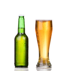 Chilled green bottle with condensate and a glass of beer
