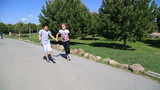 Young girl and boy holding hands and running in the nature