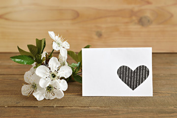 Blank card and spring flowers on wooden background