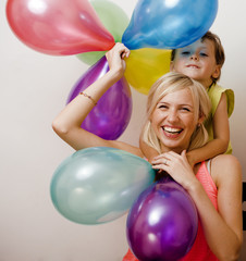 pretty family with color balloons on white background, blond wom