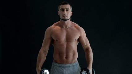 Muscular man lifting dumbbells over black background