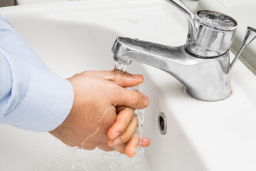 man washing his hands in the sink with water