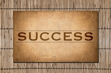 Success. The word on a stone and bamboo background