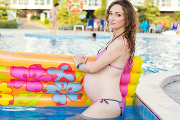 Pregnant girl with mattress near swimming pool