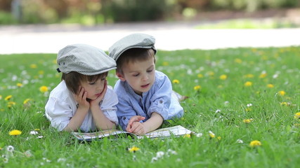 Two adorable kids, reading a book, outdoors