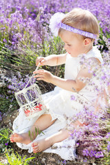 Cute child girl in field of lavender flowers