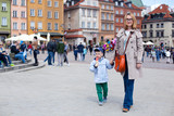 Fototapety Mam and son walking in old town Warsaw, Poland