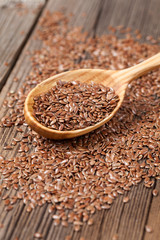Natural raw flax seeds nutritious food in spoon on wooden vintag
