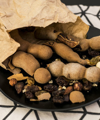 Nuts and dried fruits poured out of a paper bag on a plate
