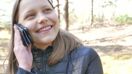Teen girl is talking by a phone in forest