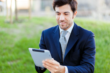 Confident businessman using a tablet outdoor