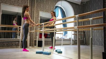 Young  girl dancer  warm up body near mirror