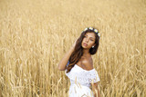 Close up portrait of a beautiful young brunette in a wheat field