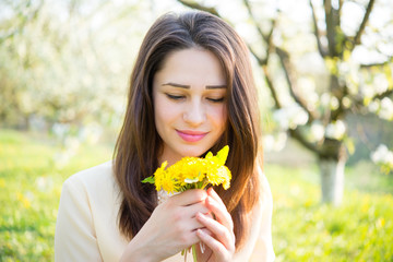 beautiful girl holding a bouquet of dandelions