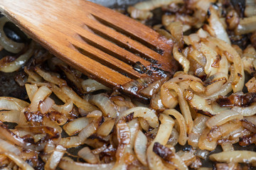 Onions caramelizing in frying pan with wooden spatula