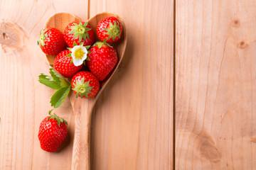 Food Hintergrund - Frische Erdbeeren auf Kochlöffel in Herzform