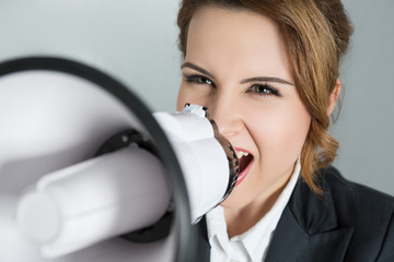 Young business woman shouting with a megaphone