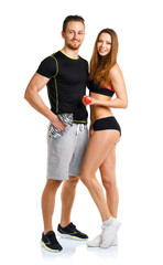 Sport couple - man and woman with dumbbells on the white