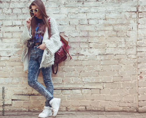 Young street fashion girl on the background of old brick wall - 82708140