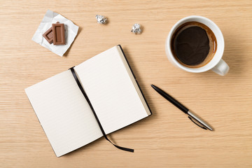Notebook, pencil, cup of coffee and chocolate on wooden table