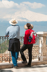 Two tourists admiring smoking Mount Etna from Castelmola