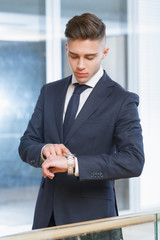 Businessman looking at his watch in the office