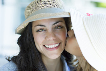 Happy mother and daughter wearing hat, smiling outdoors