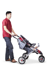 Young father pushing a baby carriage