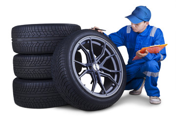 Technician checking tires isolated