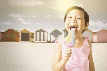 Sweet kid enjoy ice cream at shore