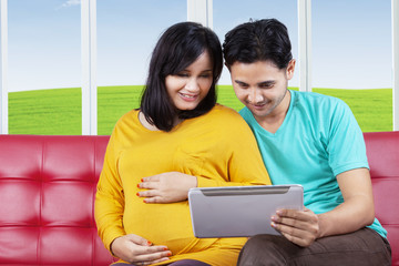 Pregnant woman using tablet with husband
