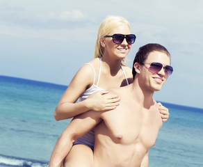 Handsome man and young beautiful woman hugging on a summer beach