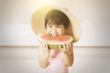 Lovely child enjoy a watermelon at coast