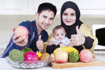 Healthy family showing thumbs-up in kitchen