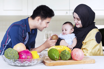 Happy parents give fruit to their child