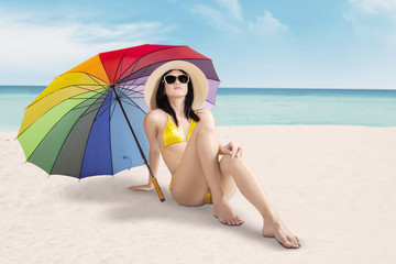 Girl sitting at shore under umbrella