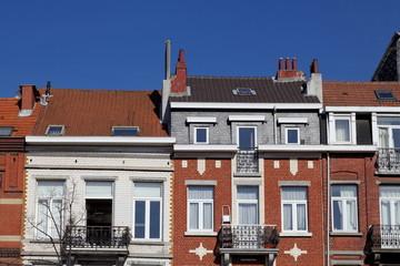 Rue de Bruxelles, maisons colorées, ciel bleu.