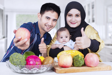 Family with thumbs-up and fruits at home