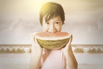 Child eats a watermelon outdoors